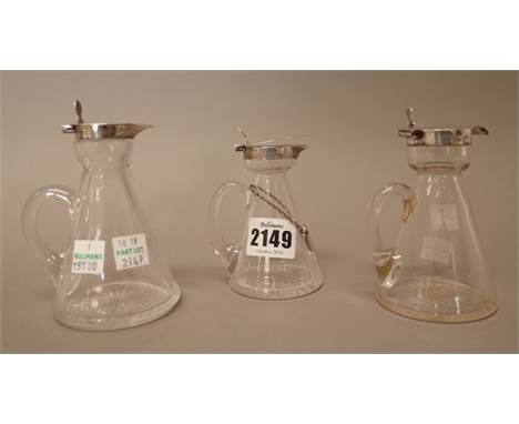 Three silver mounted glass whiskey noggins, having star cut decoration to the bases, various dates and a silver noggin label