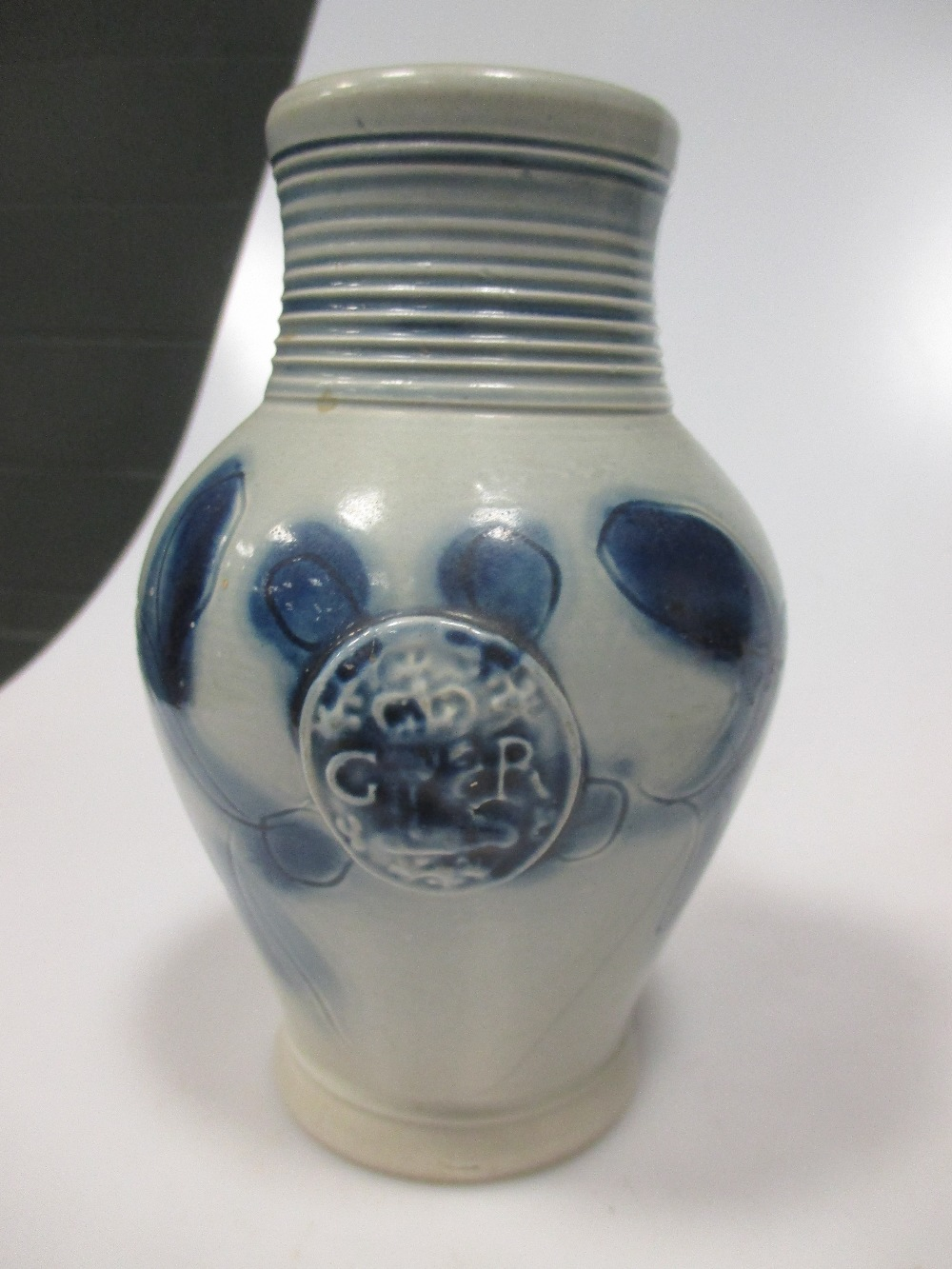 Lot 55 - An 18th century Staffordshire commemorative jug, the ovoid scratch blue decorated body moudled in