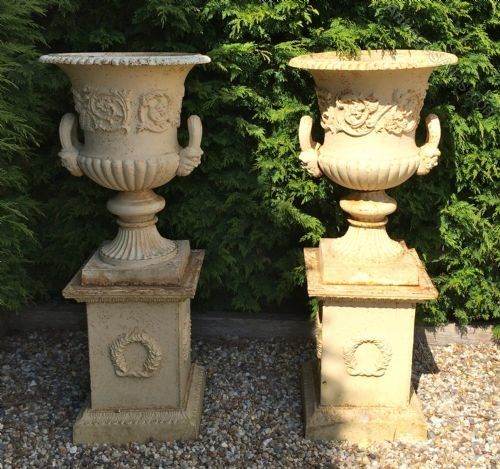Lot 34 - PAIR WHITE CAST IRON URNS ON PLINTH
