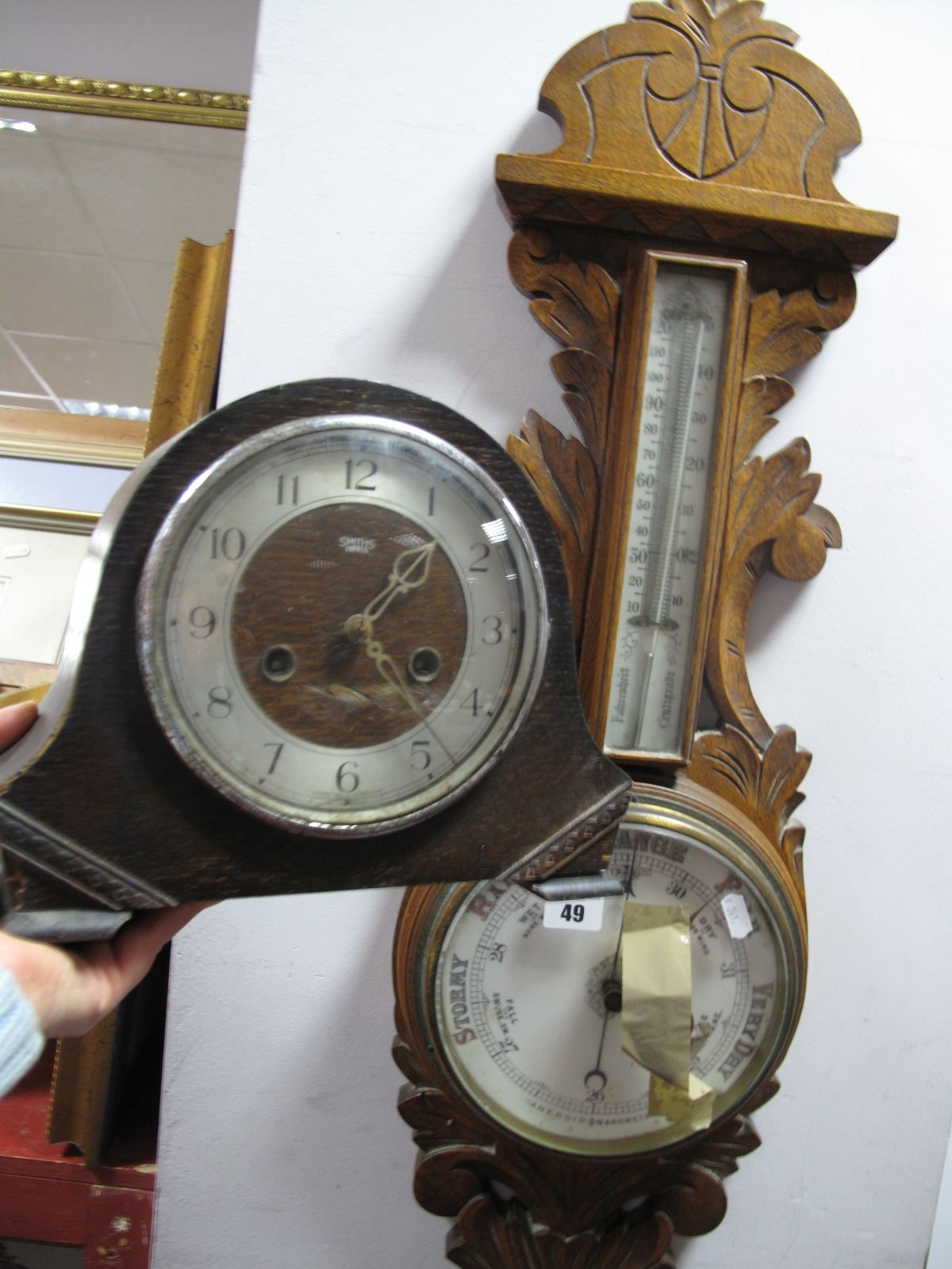 Lot 49 - An Early XX Century Oak Aneroid Barometer; together with a Smiths oak cased mantel clock. (2)