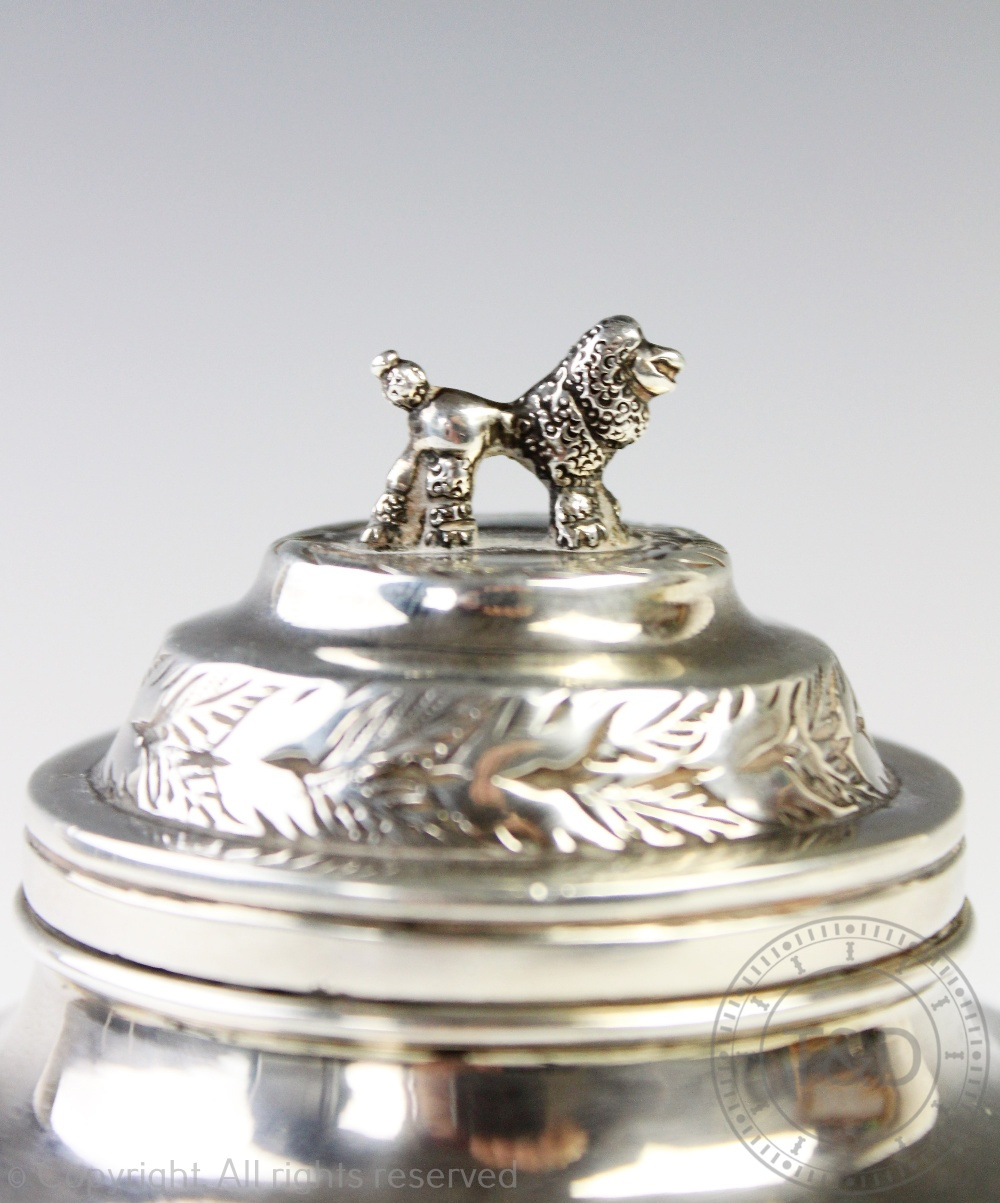 Lot 2 - A continental white metal tea canister and cover, the cover surmounted with a poodle,