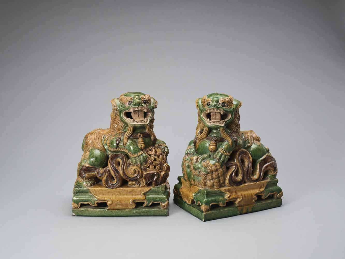 A PAIR OF RETICULATED SANCAI GLAZED POTTERY BUDDHIST LIONS, LATE MING TO EARLIER QING