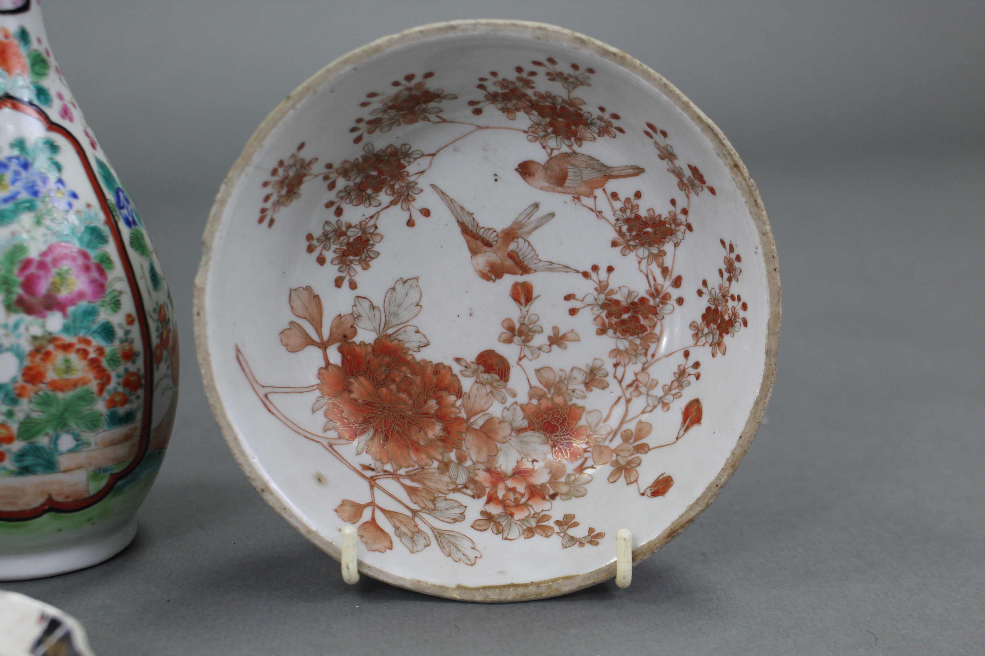 Lot 389 - An 18th century Japanese Arita saucer dish painted in blue with a circle of pine, bamboo, & prunus