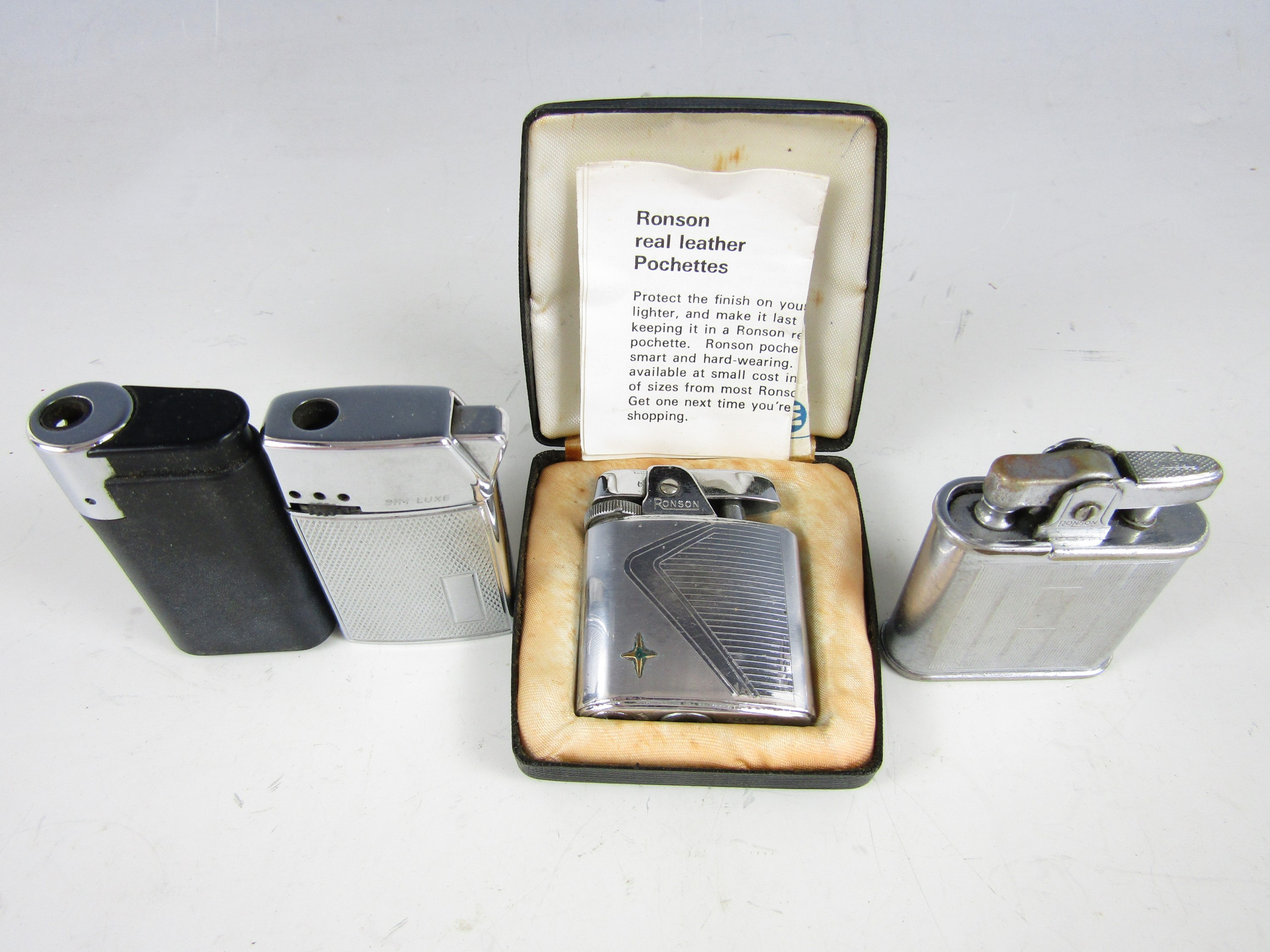 Lot 34 - A cased Ronson Varaflame cigarette lighter together with one other Ronson lighter and two others