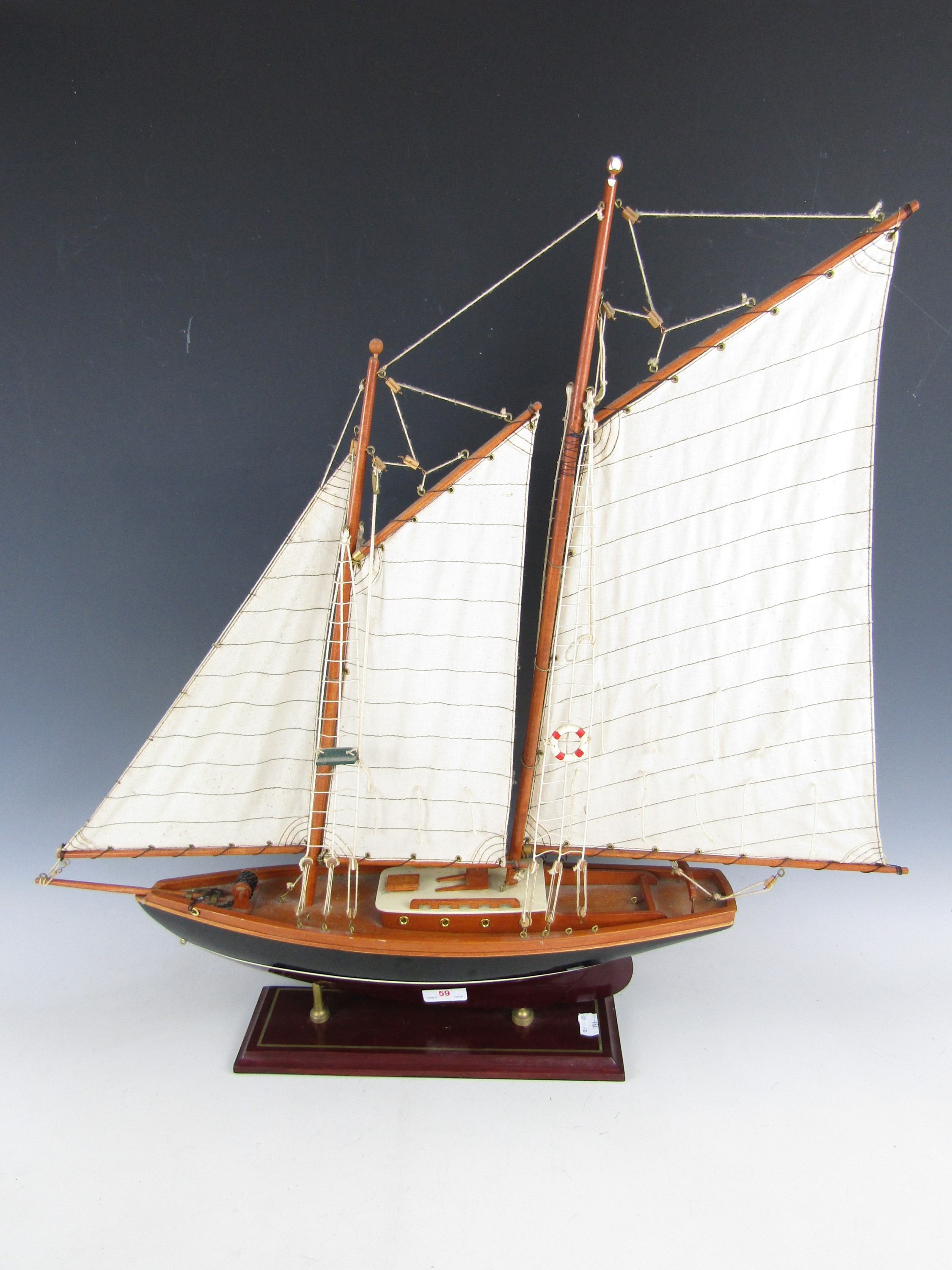 Lot 59 - A wooden scale model of a yacht with canvas sails