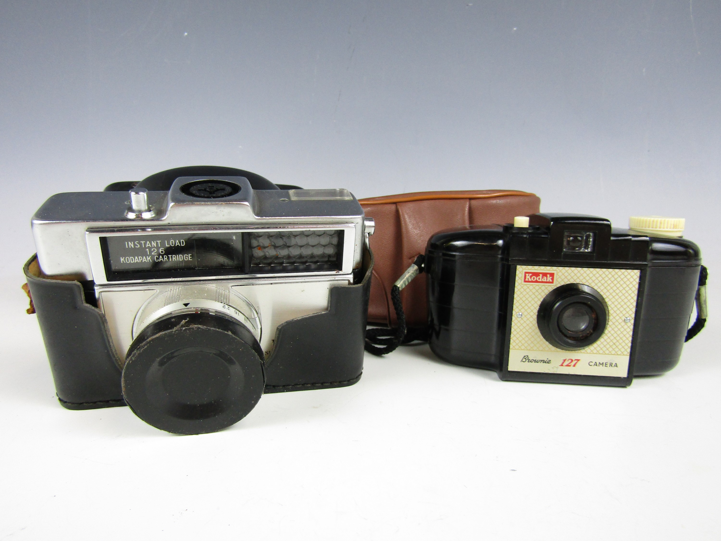 Lot 14 - A vintage Kodak Brownie 127 compact film camera together with one other similar