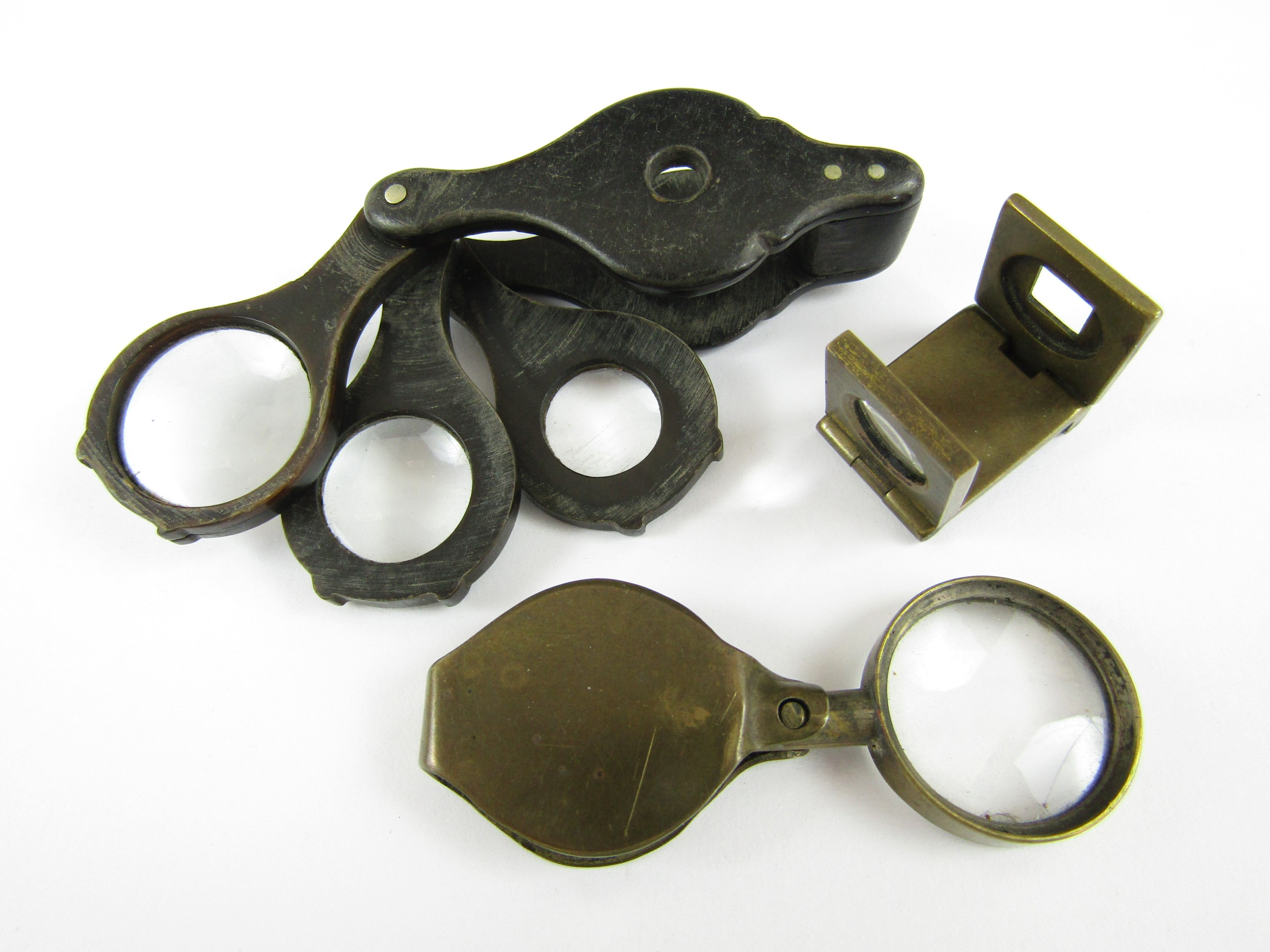 Lot 36 - A 19th Century horn folding loupe, together with a brass 'thread counting' loupe, and one other