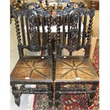 A pair of oak hall chairs, each with carved centre splat, barley-twist supports and solid seat and a