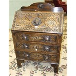 A carved oak bureau, the fall front above three drawers with lion mask handles, 75cm wide, 110cm