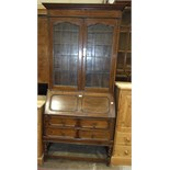 An early-20th century oak bureau/bookcase, the upper bookcase fitted with a pair of leaded light