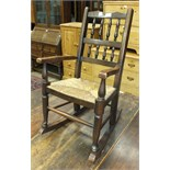 A child's stained wood rush-seated rocking chair, an oak hall stand and a small green-painted set of