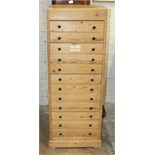 A pine narrow chest of twelve drawers, 45.5cm wide, 123cm high.