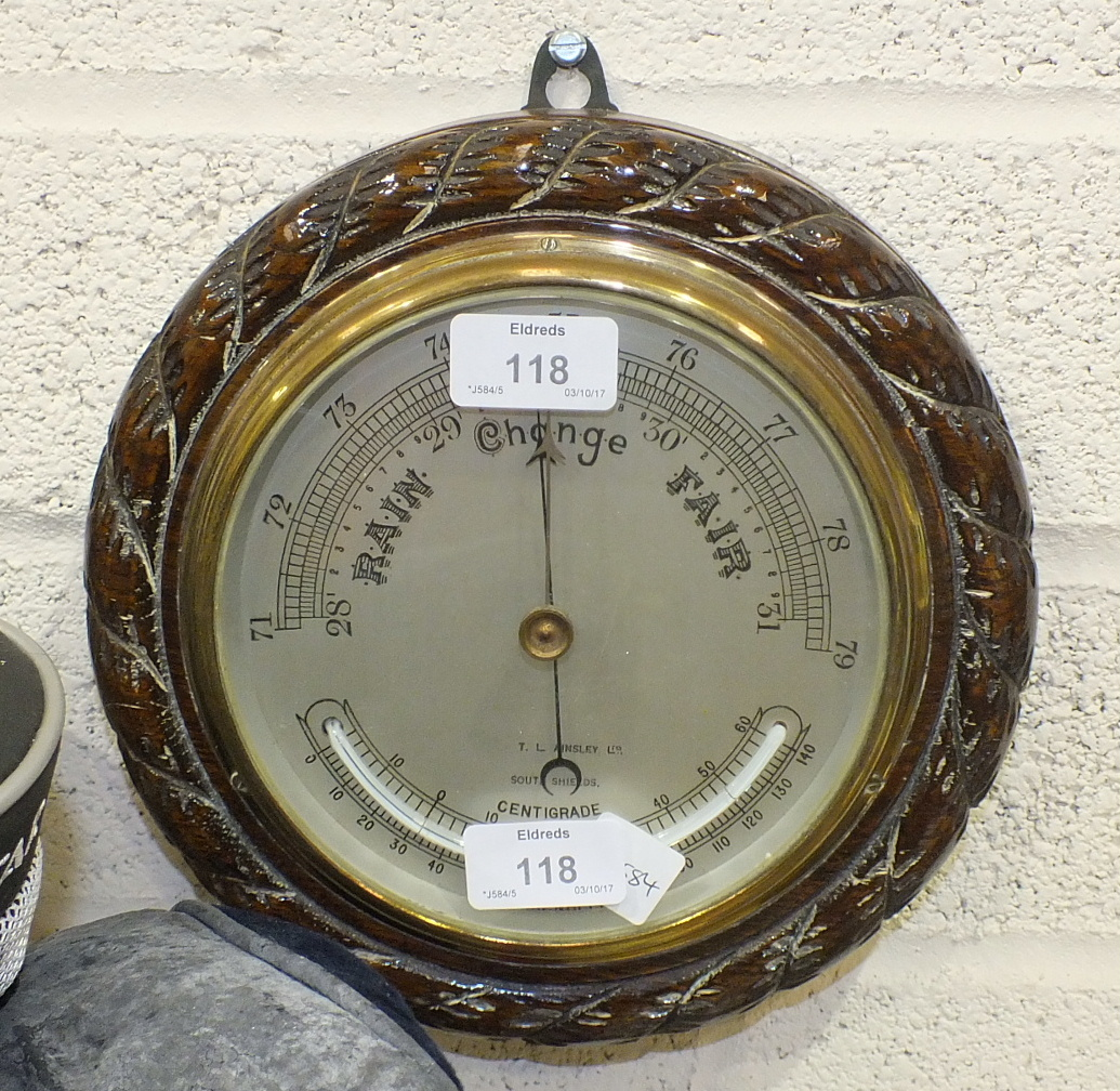 Lot 118 - T L Ainsley Ltd, South Shields, a circular aneroid barometer/thermometer within a wooden rope-