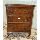 A 'Jaycee' low walnut bedside chest, the hinged rectangular fold-over top above three drawers, on