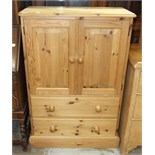 A modern pine low cupboard, the rectangular top above a pair of doors and two drawers, 76cm wide,