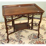 An Oriental hardwood tray-top table with pierced frieze, on folding stand united by an undertier, 81