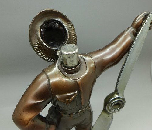 Lot 602 - A figural table lighter in the form of an airman with propeller,