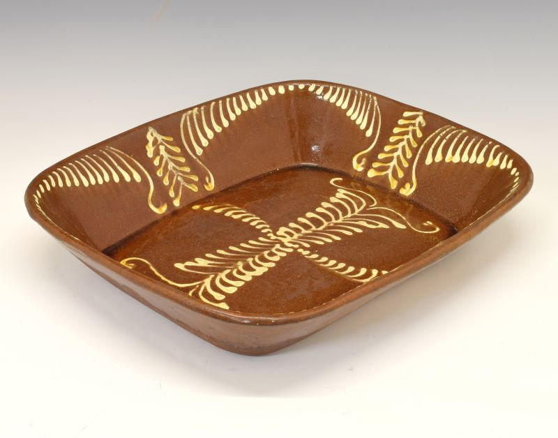 Large 19th Century slipware pottery baking dish of rounded oblong form, 49cm wide