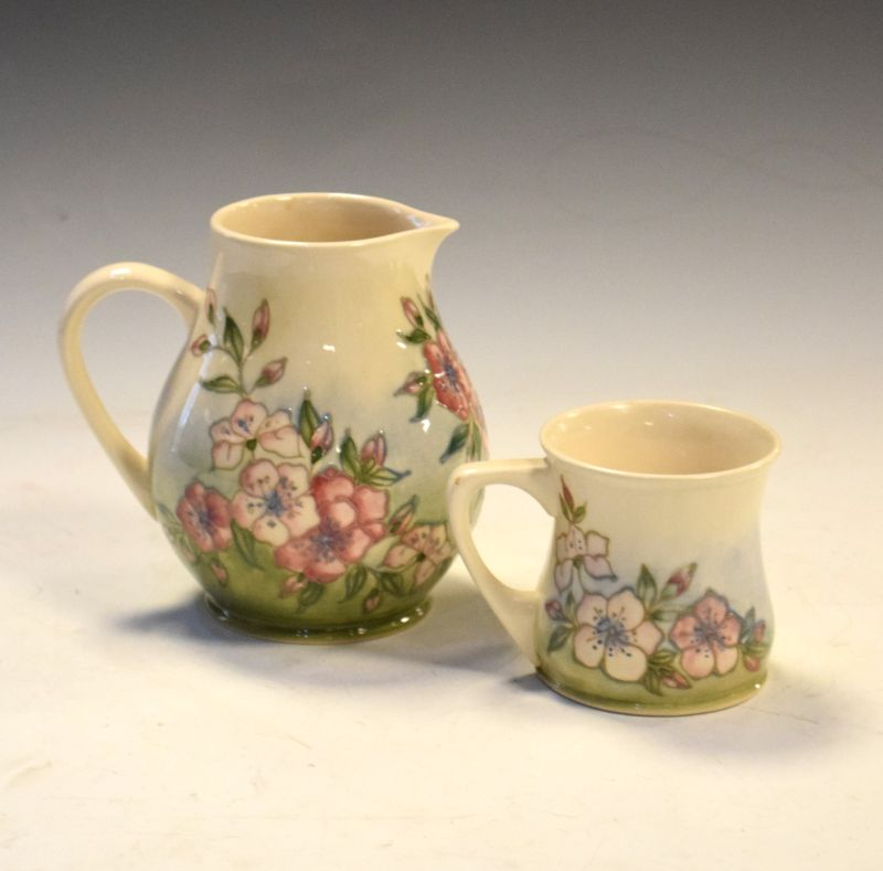 Moorcroft pottery Dog Rose pattern jug and mug, each of bulbous form, the larger 14cm high