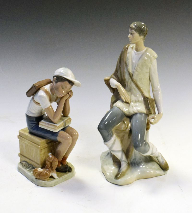 Two Lladro porcelain figures comprising: a seated shepherd, 26cm high and a school boy with small