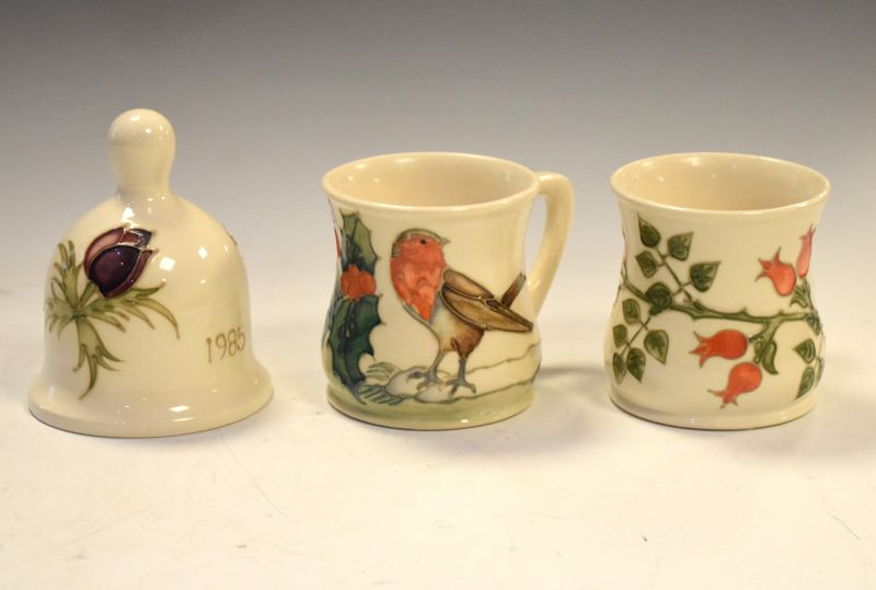 Three items of Moorcroft pottery comprising: Robin mug, Rosehip mug and Anemone bell dated 1985 (3)