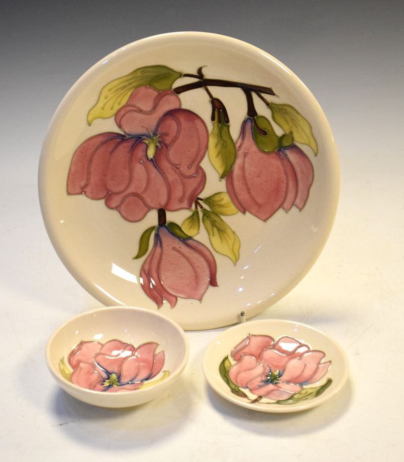 Three items of Walter Moorcroft Magnolia pattern pottery comprising: a plate, 26cm diameter, bowl,