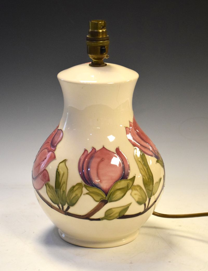 Walter Moorcroft pottery Magnolia pattern lamp of bulbous form with tube-line decoration on a