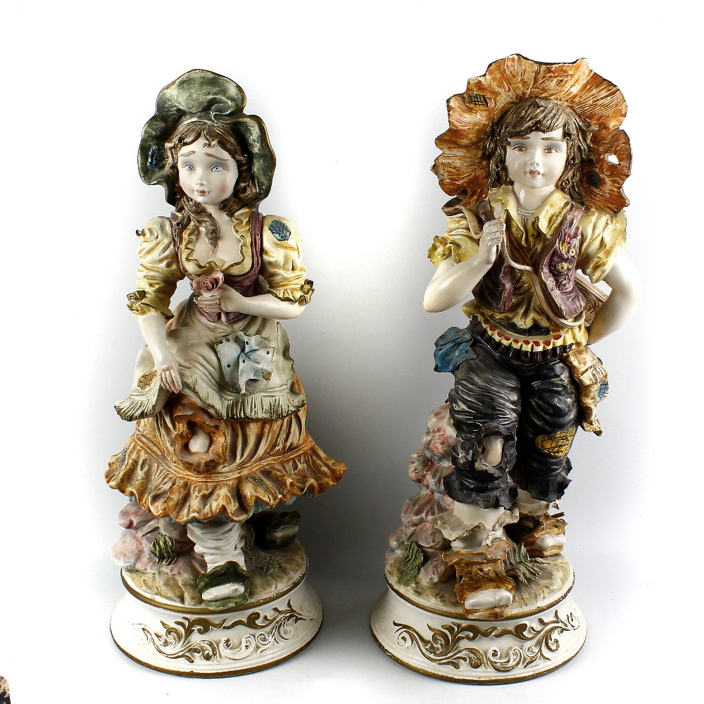 Lot 103 - A large pair of Capodimonte figures Modelled as a boy and girl, he with rifle slung across his back,