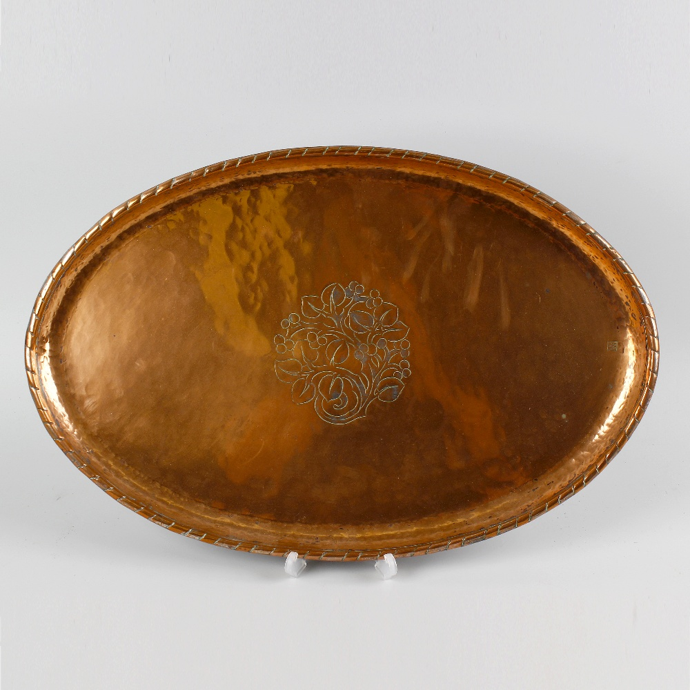 Lot 394 - An Arts and Crafts oval copper dish by Hugh Wallis, the central panel, decorated with an engraved