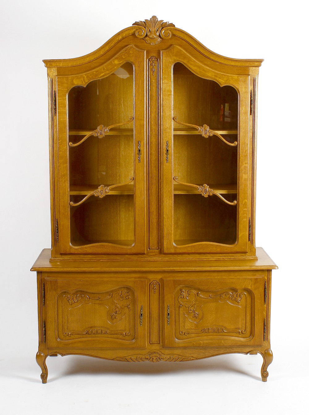 Lot 840 - A reproduction oak display cabinet. The upper section with carved scrolled pediment above twin