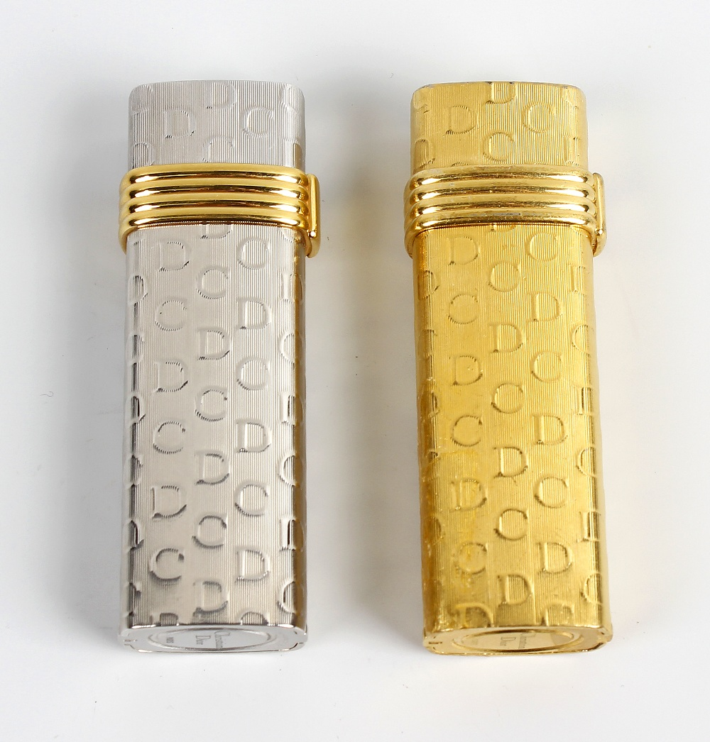 Lot 266 - A pair of lighters by Christian Dior. Comprising a white gold plated example stamped Plaque OR G,