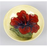 A small Walter Moorcroft dish. Of shallow form having central orchid flower upon a merging pale