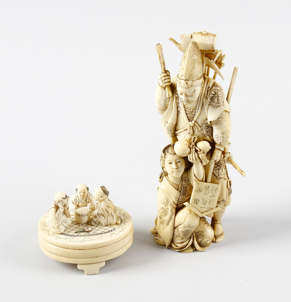 Lot 340 - A 19th century carved ivory okimono, modelled as a male laden with sword and other tools, a female