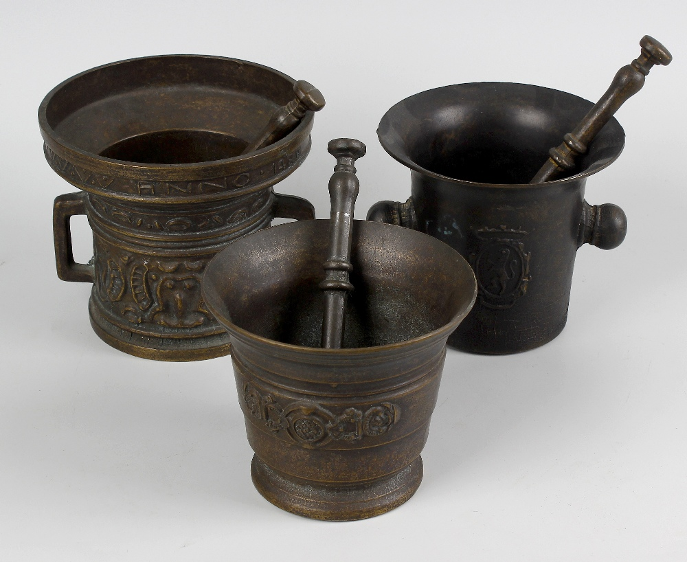 Lot 575 - A box containing seven assorted cast mortars with pestles. The largest in 15th century style with