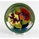 A Walter Moorcroft pottery dish. Decorated in the Hibiscus pattern on glazed green ground, with