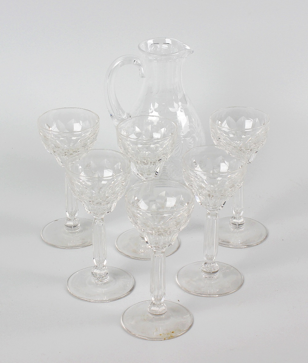 Lot 32 - A glass sherry jug plus six glasses. The jug of pear form raised upon circular footed base, and