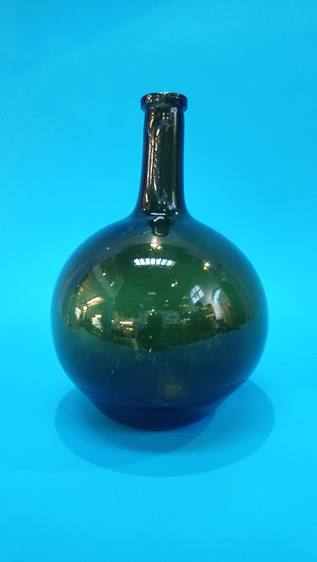 Lot 26 - An 18th century green glass bulbous shaped wine bottle. 27 cm high