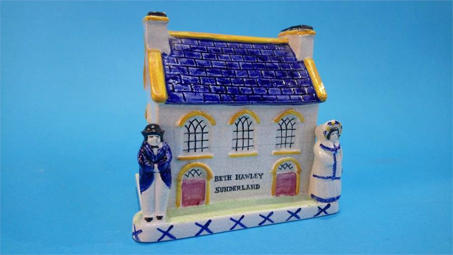 Lot 27 - A 19th Century Staffordshire house money box, with two figures standing either side of the house, to