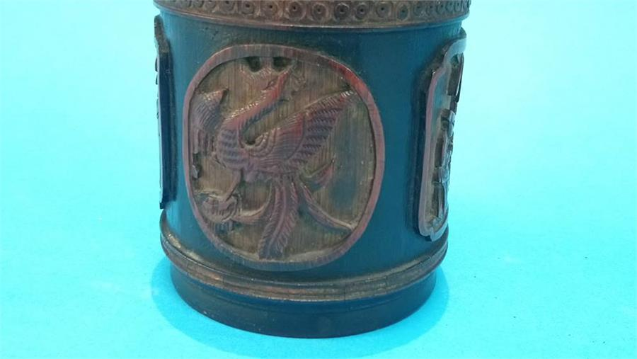 Lot 62 - A carved bamboo canister, decorated with panels of figures and dragons. 14 cm high