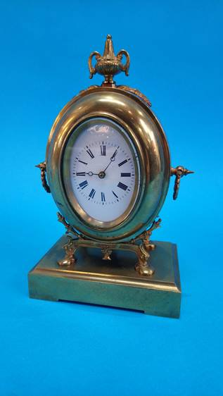 Lot 41 - A small brass mantel clock with oval enamelled dial, stamped S. and F. 23cm high