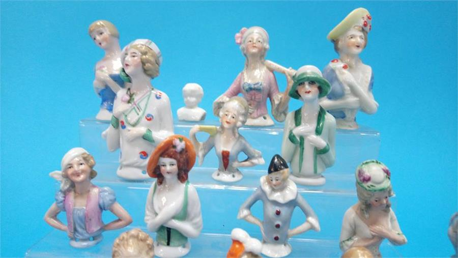 Lot 40 - A collection of twenty one Continental porcelain figure heads and a small pair of Continental