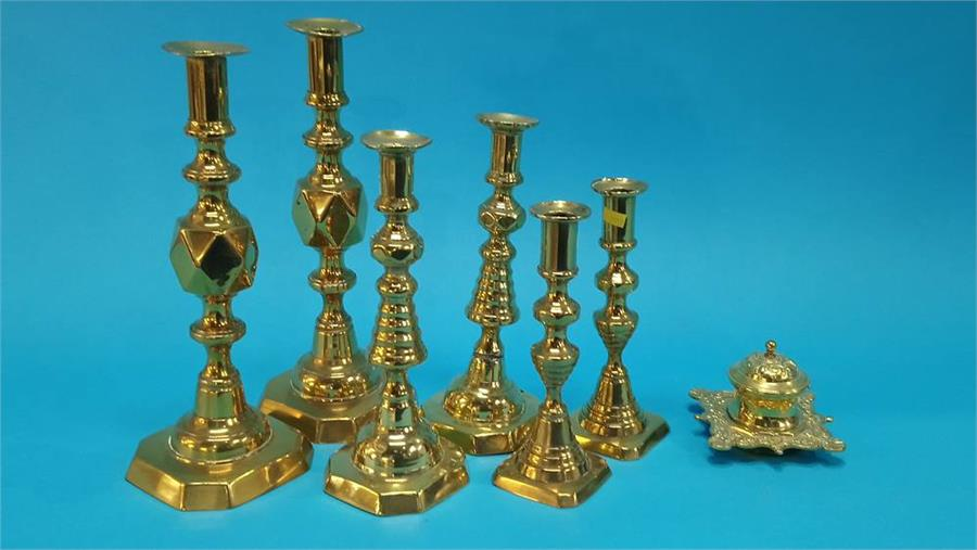 Lot 64 - A small brass inkwell and three pairs of candlesticks. (7)