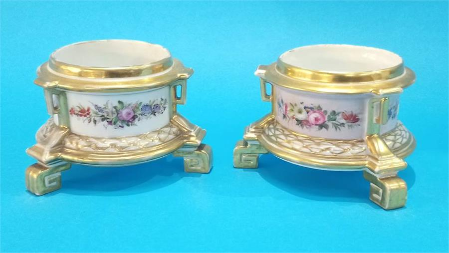 Lot 70 - A pair of Continental porcelain stands, decorated with flowers and having Greek key feet. 9cm high