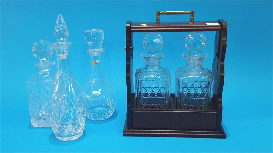 Lot 65 - A modern tantalus and three glass decanters.
