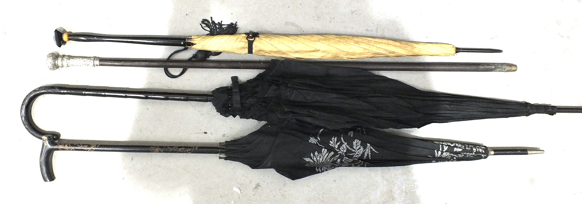 Lot 102 - A silver-mounted walking cane and three wooden-handled parasols, (4).