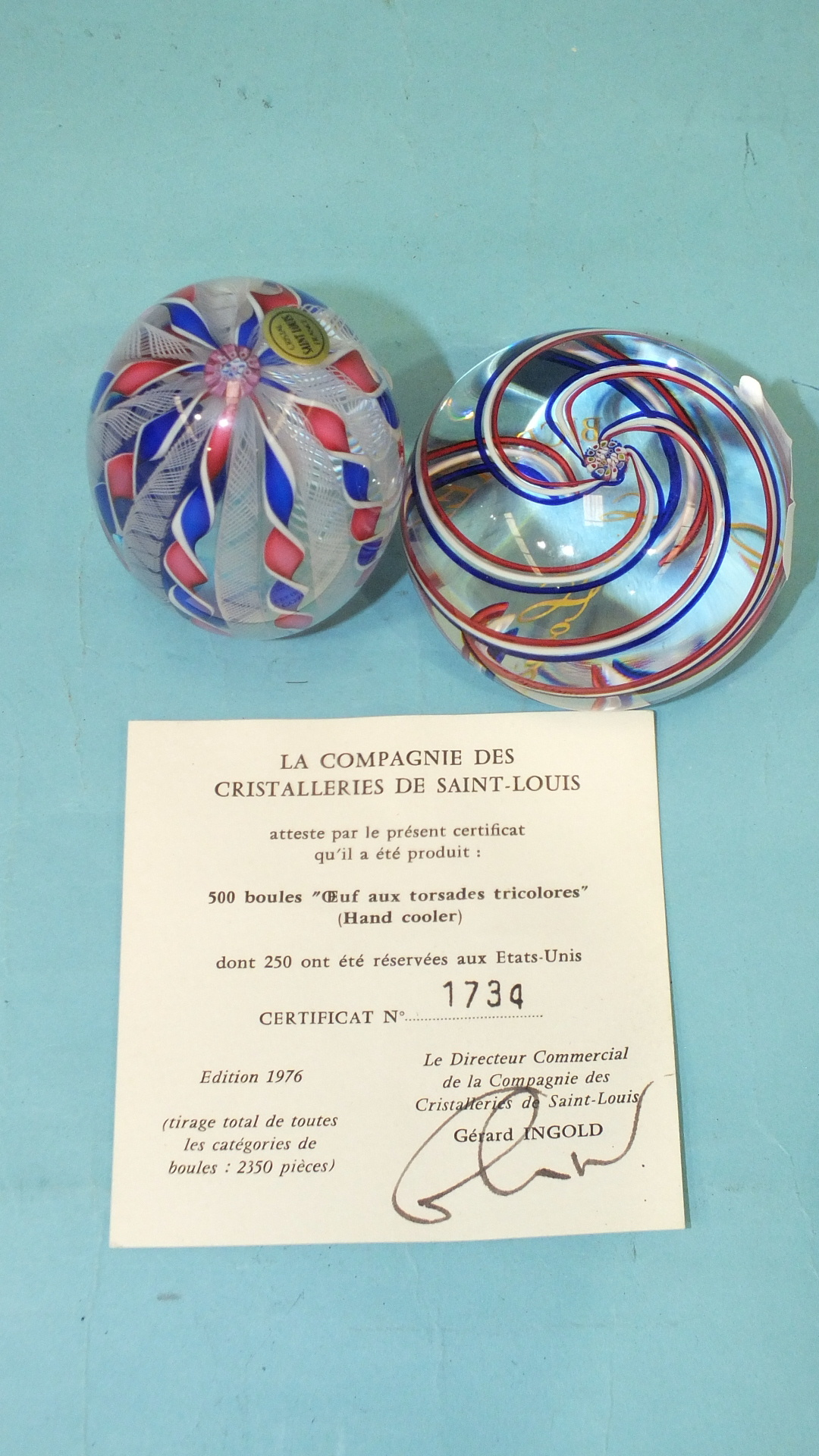Lot 258 - A modern St Louis glass paperweight of egg shape, with twists of tricolour, dated 1976, 7.5cm,