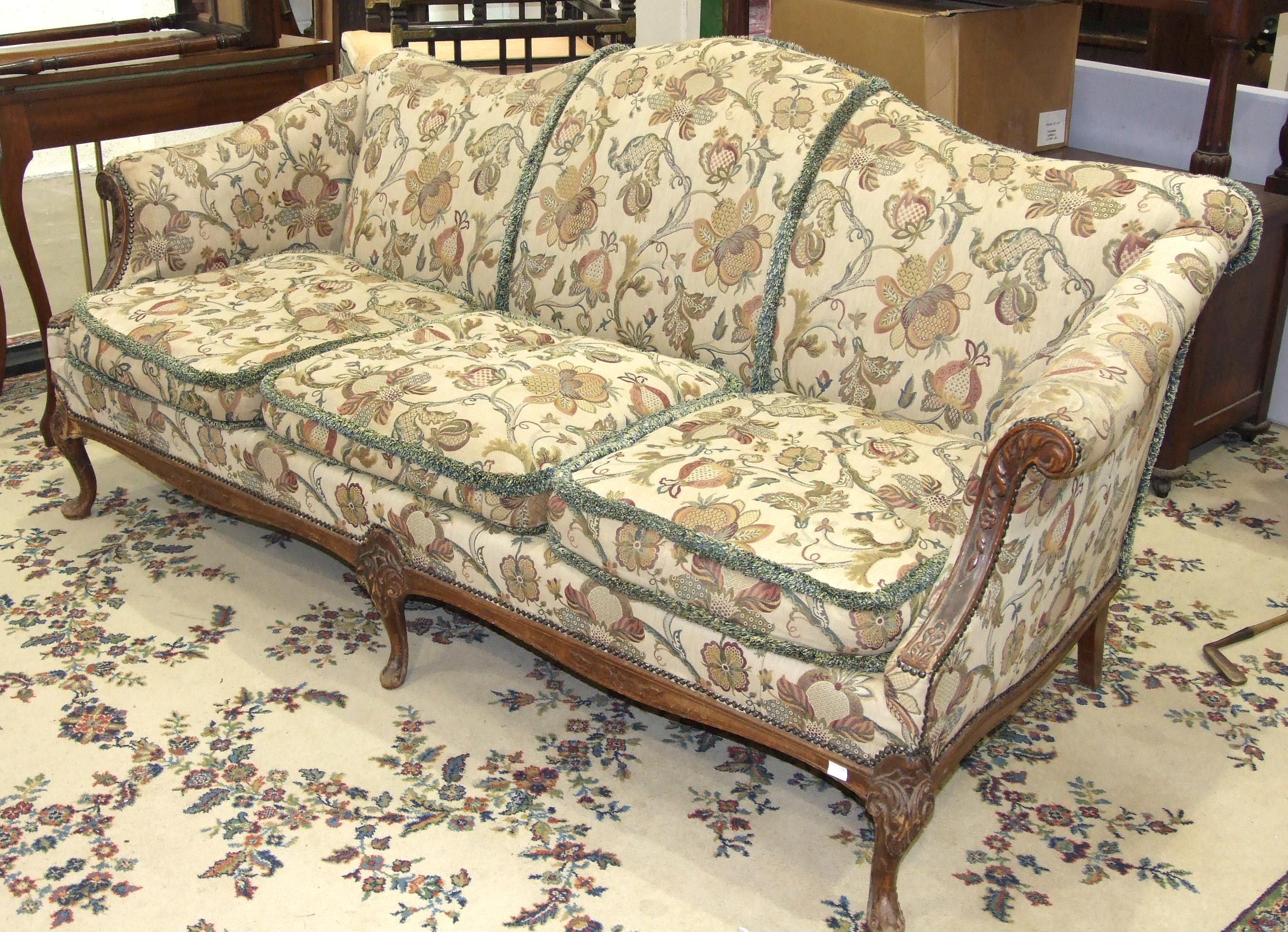 A walnut-framed three-seat sofa raised on short carved cabriole legs, 213cm wide.