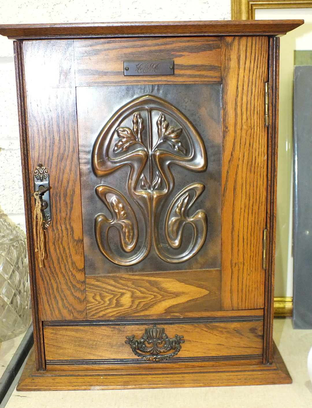 A smoker's small compendium cabinet, the door with Art Nouveau-style copper panel enclosing a fitted