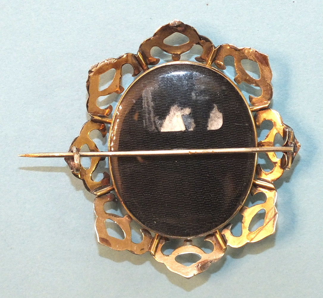Lot 173 - A Victorian mourning brooch, the front locket containing a photograph of a gentleman, within