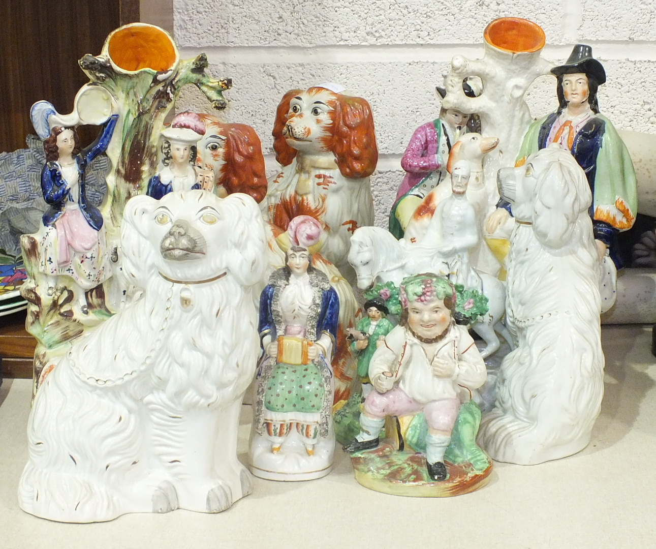 A collection of Staffordshire flat-back figures and Staffordshire spaniels, (some restoration and